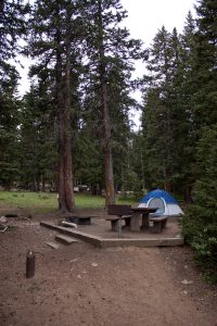 photo shows a campsite set up with a tent and fire pit