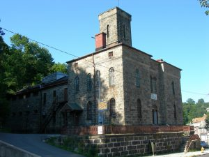 photo shows the old jail museum, with grey bricks and a large towering guard turret.