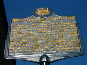 "photo shows a commemorative plaque of the molly maguire executions that reads ""in june 21st 1877 four molly maguires, an alleged secret society of irish mine workers were hanged here"""
