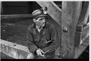 photo is an antique picture of a dirty coal miner sitting on a wooden trestle.