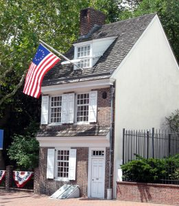Photo shows the façade of the Betsy Ross house, with an American flag hanging from the upper window, billowing in a breeze.