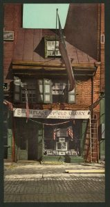 """Photo shows a postcard with a picture of the Betsy Ross House as it looked in antiquity. The sign on the front says """"Birthplace of Old Glory, open to the public."""""""
