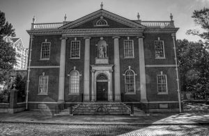 Photo shows the façade of the American Philosophical Library in black and white. The statue of Ben Franklin sits on top of the front door in a small alcove.