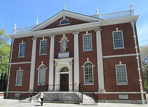 Photo shows the front of the American Philosophical Library during the day, there are four large pillars and red brick. The statue of Ben Franklin is sitting atop the front door in a small alcove.